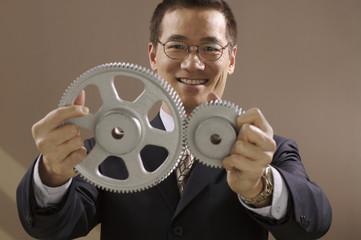 Asian businessman holding gear wheels