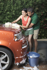 Hispanic couple washing car in driveway