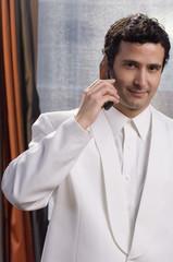 Hispanic man in tuxedo talking on cell phone