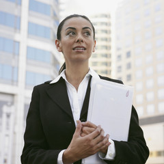 Hispanic businesswoman holding paperwork