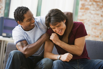 Multi-ethnic men hugging on sofa