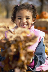 African girl playing in leaves