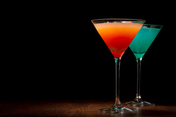 Red and blue cocktails on a black background