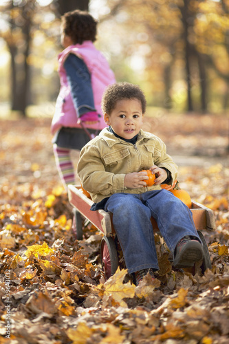 African girl pulling brother in wagon