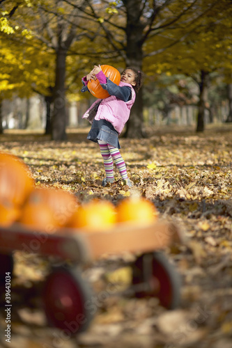 African girl carrying pumpkin