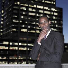 African businessman on balcony at night