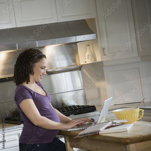 Pregnant African woman typing on laptop