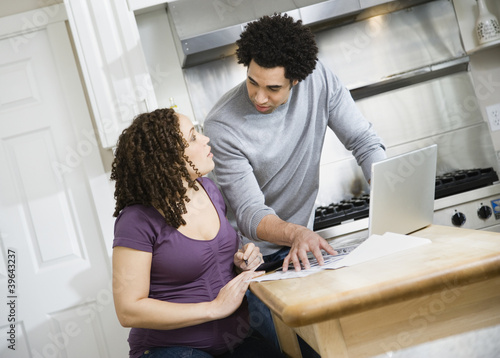 Pregnant African couple paying bills