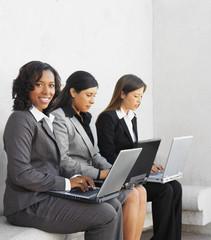 Multi-ethnic businesswoman typing on laptops