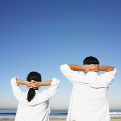 Hispanic couple with hands behind head at beach