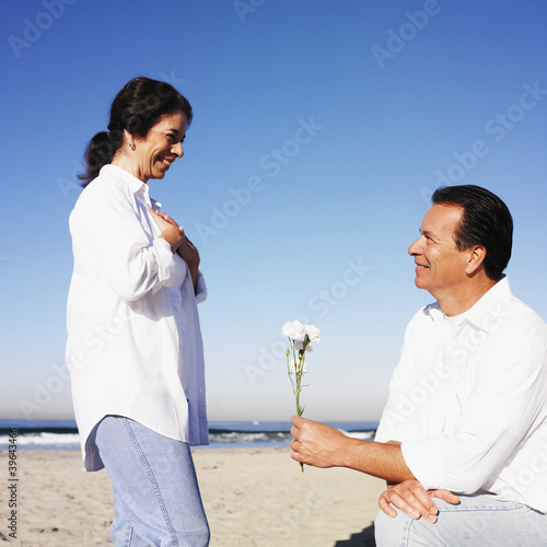 Hispanic man giving flower to wife
