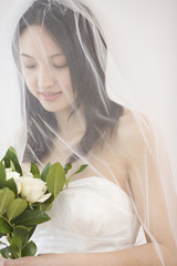 Asian bride holding flower bouquet