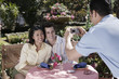 Waiter taking photograph of couple at table