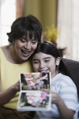 Hispanic mother and daughter looking at photo album