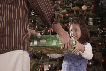 Hispanic father and daughter exchanging Christmas gift