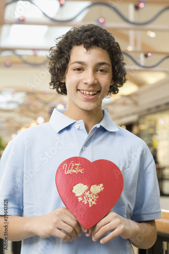 Multi-ethnic teenage boy holding Valentine's Day heart