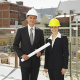 Businesspeople wearing hard hats at construction site