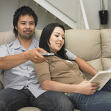 Multi-ethnic couple relaxing on sofa