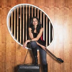 Hispanic woman holding electric guitar