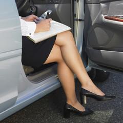 Eurasian businesswoman working in car
