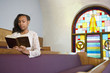 African American woman reading Bible in church