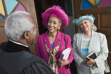 Senior African American women talking to Reverend
