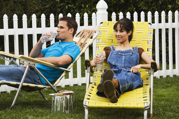 Multi-ethnic couple relaxing in lawn chairs