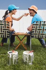 Multi-ethnic couple eating near newly painted fence