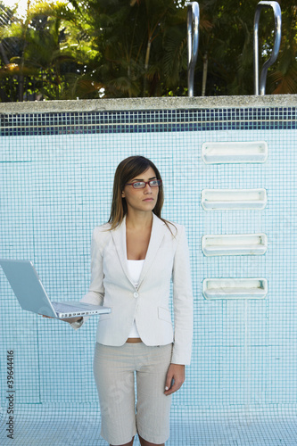 South American businesswoman in empty swimming pool