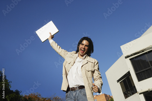 South American man holding laptop over head