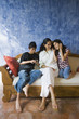 Hispanic mother and children relaxing on sofa
