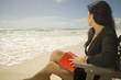 Hispanic woman with book at beach