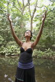 Hispanic woman with arms raised in woods