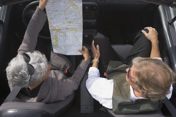 Senior couple looking at map in car