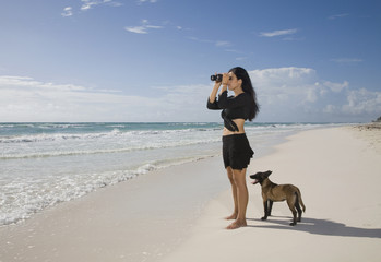 Hispanic woman using binoculars at beach