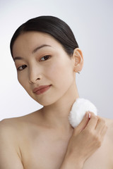 Asian woman applying powder
