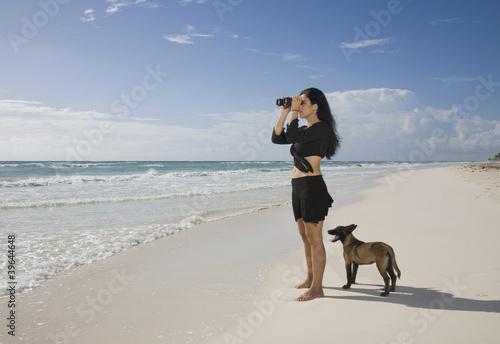 Hispanic woman using binoculars at beach
