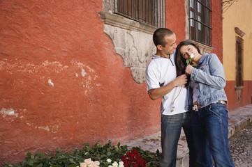 Hispanic couple holding rose