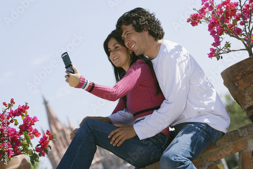Hispanic couple taking own photograph