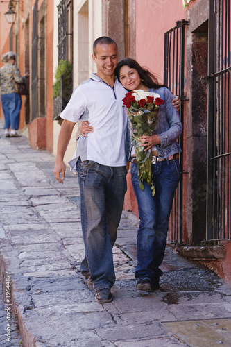 Hispanic couple on sidewalk with roses
