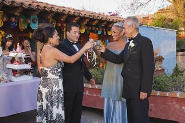 Hispanic couples toasting at Quinceanera