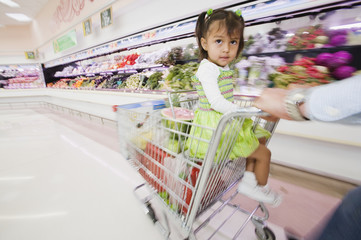 Hispanic girl in shopping cart