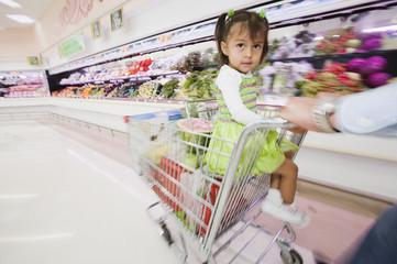 Hispanic girl in shopping cart