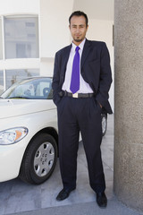 Hispanic car salesman next to new car