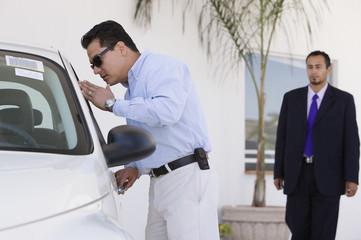 Hispanic man looking at new car