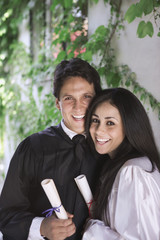 Man and woman holding college diplomas