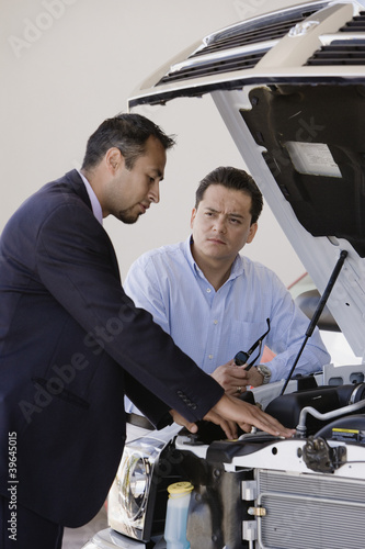 Hispanic man talking to car salesman