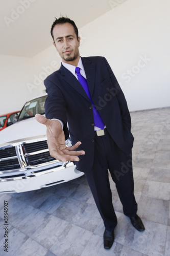 Hispanic car salesman extending handshake