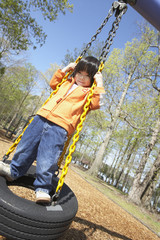 Asian child standing on tire swing