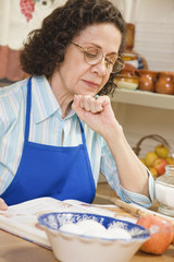 Senior Hispanic woman reading cook book